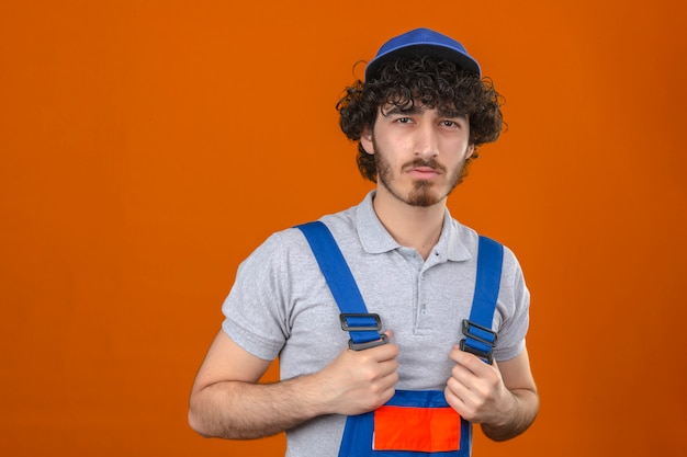 Young bearded handsome builder wearing construction uniform and cap standing with disapproving expression on face negative person over isolated orange wall