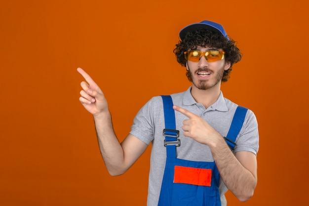 若い建設ひげを生やしたハンサムなビルダーひげを生やした眼鏡とキャップ笑顔と孤立したオレンジ色の壁を越えて側に2本の手と指で指しているカメラを見てキャップ