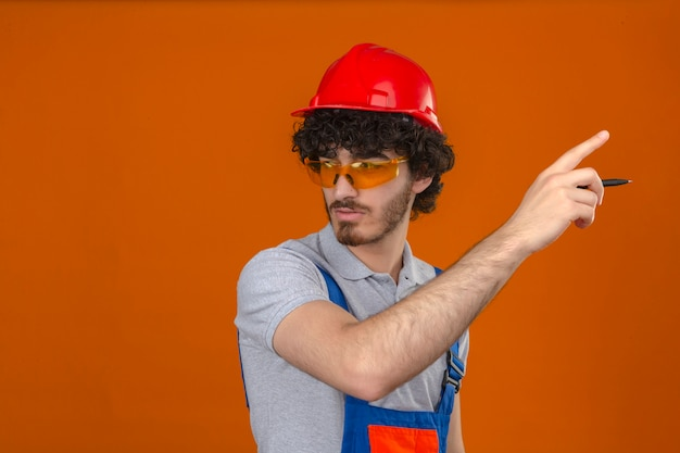 Young bearded handsome builder wearing construction uniform glasses and safety helmet looking aside holding pen in hand and pointing with serious face over isolated orange wall