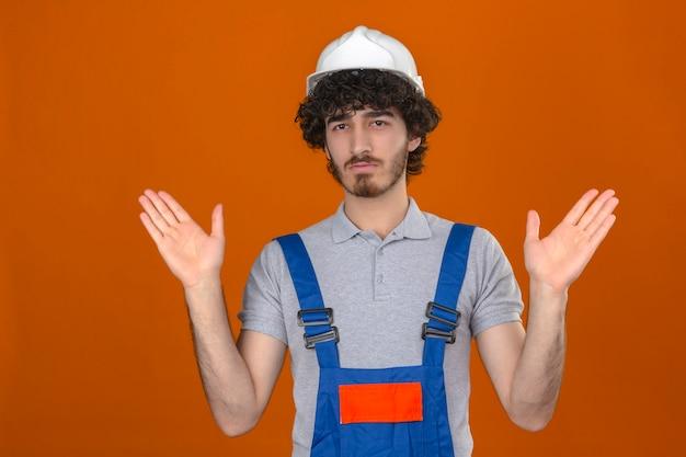 Il giovane costruttore bello barbuto che indossa l'uniforme della costruzione e l'elmetto di sicurezza clueless e confusi con a braccia aperte nessun concetto di idea che controlla la parete arancio isolata