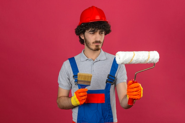 Young bearded handsome builder wearing construction uniform and safety helmet holding brush and paint roller looking at in with serious frowning face over isolated pink wall