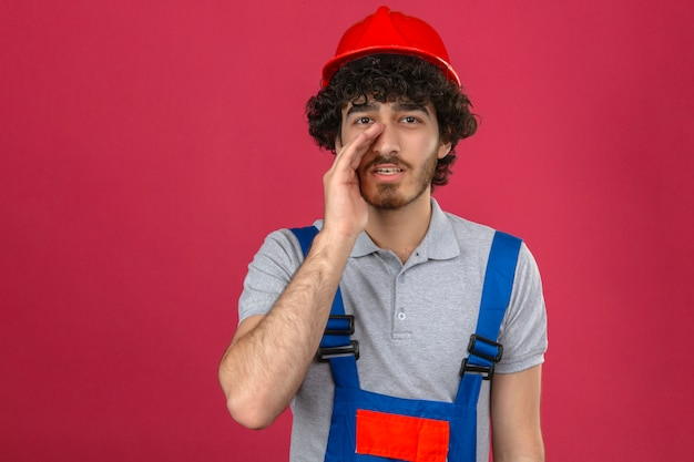 Young bearded handsome builder wearing construction uniform and safety helmet shouting with palm near mouth over isolated pink wall
