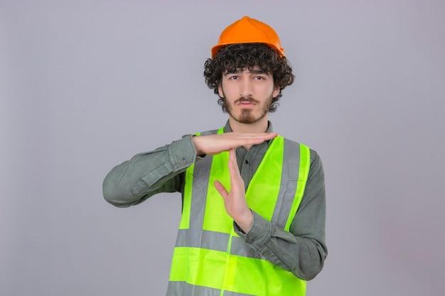 Giovane ingegnere bello barbuto che sembra gesto di timeout di fabbricazione sovraccarico con le mani che controllano parete bianca isolata