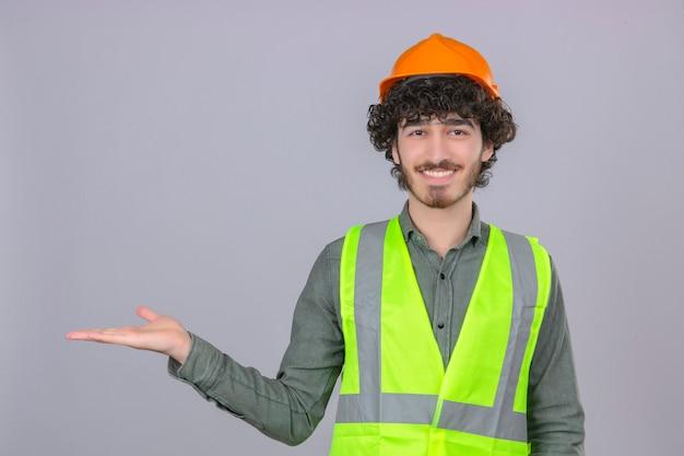 Spazio sorridente di presentazione allegro sorridente della giovane ingegnere bello barbuto e indicare con il palmo della mano che esamina la macchina fotografica sopra la parete bianca isolata