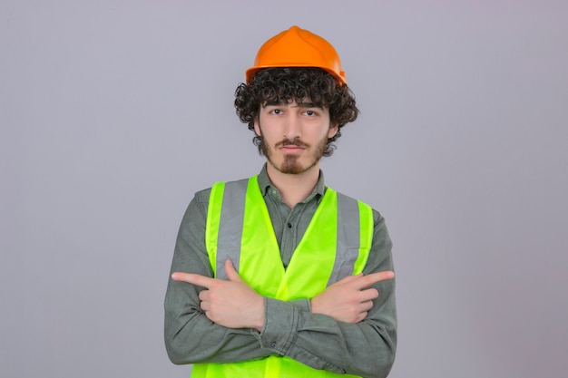 若いひげを生やしたハンサムなエンジニア立っている交差した腕と人差し指で側に分離の白い壁に深刻な顔で側を指して