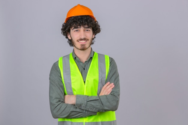 分離の白い壁に優しい笑みを浮かべて組んだ腕と立っている若いひげを生やしたハンサムなエンジニア