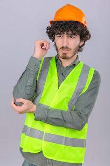 Молодой бородатый красивый инженер трогает его локоть, чувствуя боль, стоя с несчастным лицом над изолированной белой стеной