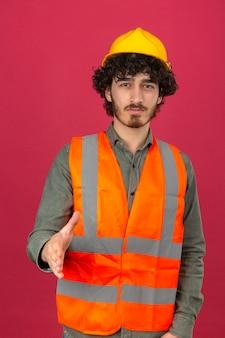Молодой бородатый красивый инженер в шлеме безопасности и жилете делает приветственный жест, предлагая руку, глядя в камеру с улыбкой над изолированной розовой стеной