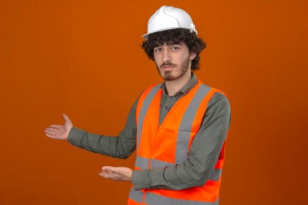 セキュリティヘルメットとベストを提示し、孤立したオレンジ色の壁に深刻な顔でカメラを見て手のひらで指しているハンサムなエンジニアを生やした若いひげを生やした