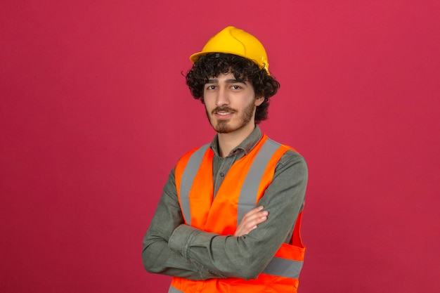 分離されたピンクの壁の上の顔に笑顔で腕を組んでセキュリティヘルメットとベスト立って身に着けている若いひげを生やしたハンサムなエンジニア