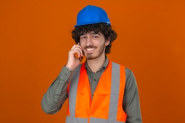 젊은 잘 생긴 엔지니어 보안 헬멧을 착용하고 고립 된 오렌지 벽 위에 친절 웃는 휴대 전화 얘기 조끼