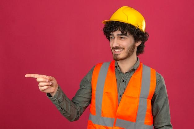 Casco e giubbotto di sicurezza d'uso del giovane ingegnere bello barbuto che guardano da parte indicando qualcosa con il dito che sorride sopra la parete rosa isolata