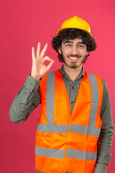 Young bearded handsome engineer wearing security helmet and vest smiling doing ok sign standing over isolated pink wall