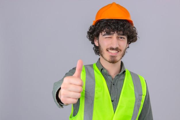 Молодой бородатый красивый инженер, подмигивая с улыбкой на лице, показывает палец вверх над изолированной белой стеной