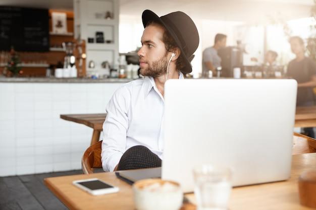 Молодой бородатый хипстер в модной шляпе, слушающий музыку или аудиокнигу в белых наушниках, сидя за деревянным столом с портативным компьютером и сотовым телефоном с пустым экраном во время обеда в уютной кофейне