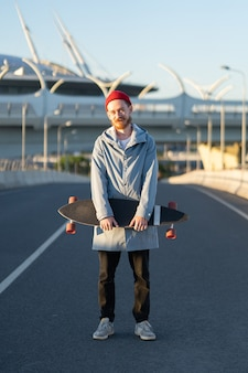 Young bearded hipster man in red hat hold longboard in city street trendy urban lifestyle concept
