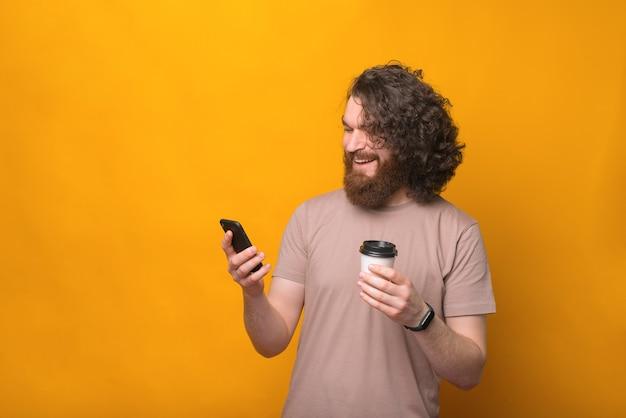 スマートフォンを使用して笑って、コーヒーを持って奪う若いひげを生やしたヒップスターの男