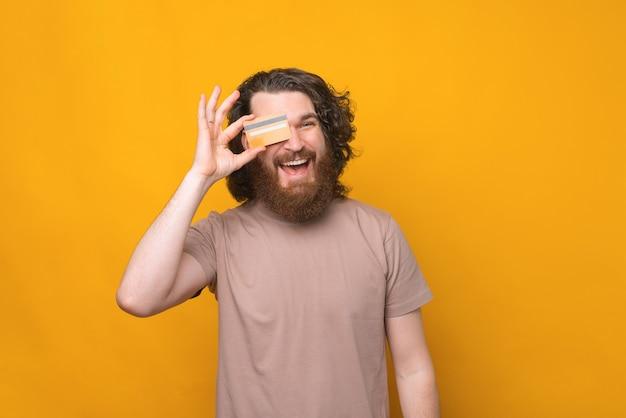 신용 카드를 보여주는 긴 곱슬 머리를 가진 젊은 수염 된 hipster 남자