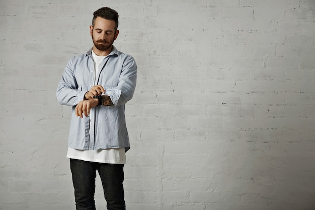 白いレンガの壁で彼の腕に入れ墨を示す彼のカジュアルなライトデニムシャツの袖を巻く若いひげを生やしたヒップスター