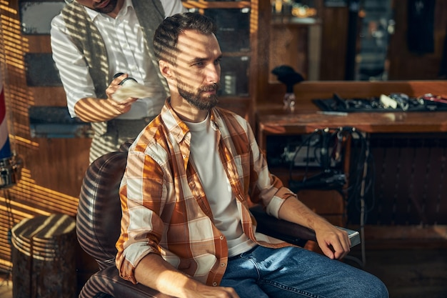 Young bearded hipster sitting in an armchair at a barbershop while his hair-stylist getting ready to shave him