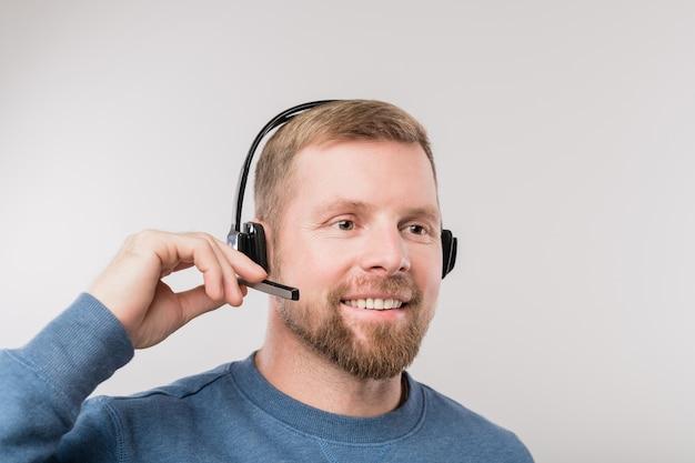 Молодой бородатый оператор горячей линии в наушниках и синем пуловере консультирует клиентов перед камерой