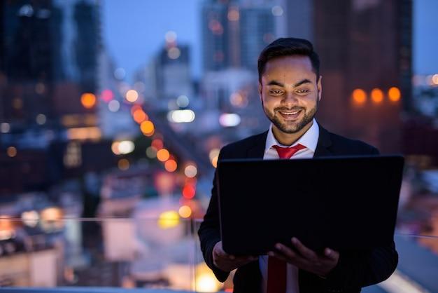 Молодой бородатый индийский бизнесмен против вида на город ночью