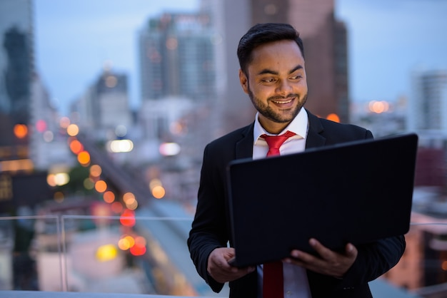 Молодой бородатый индийский бизнесмен против вида на город
