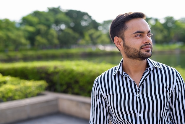 若いひげを生やしたインドのビジネスマンが公園でリラックス