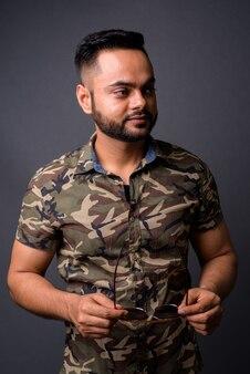 灰色に対して若いひげを生やしたインド人