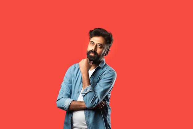 疑いを持って、赤の上に立っている間、混乱した表情で若いひげを生やしたインド人