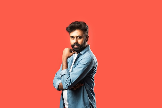 Young bearded indian man having doubts and with confuse face expression while standing on red