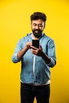 Young bearded indian man using smartphone, smiling while calling or chatting with friend, standing on yellow