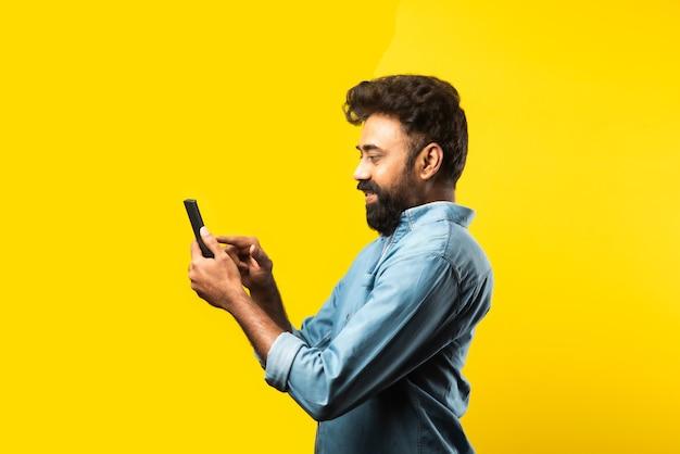 スマートフォンを使用して、電話や友人とチャットしながら笑顔、黄色の上に立っている若いひげを生やしたインド人