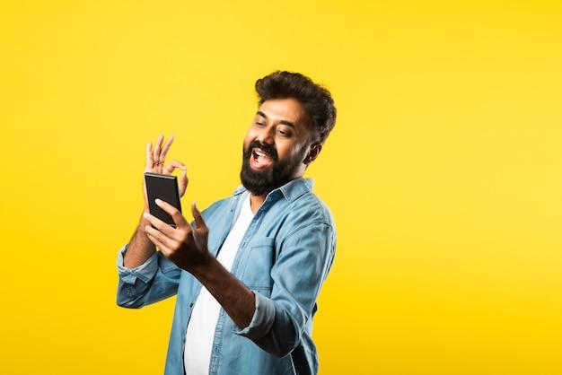 Молодой бородатый индийский мужчина с помощью смартфона, улыбаясь, звоня или болтая с другом, стоя на желтом