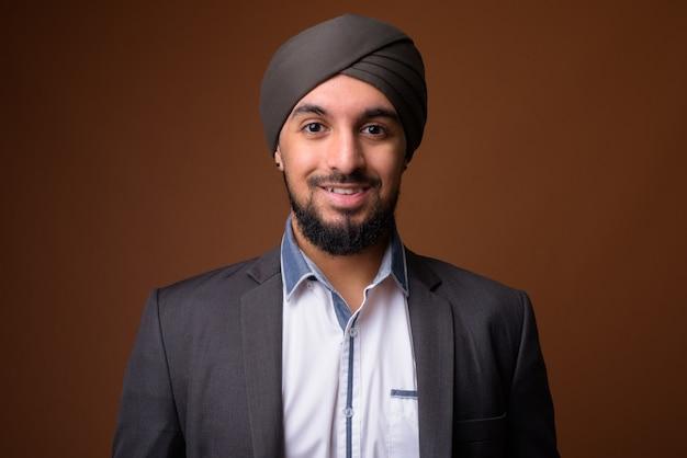 Молодой бородатый индийский сикхский бизнесмен в тюрбане