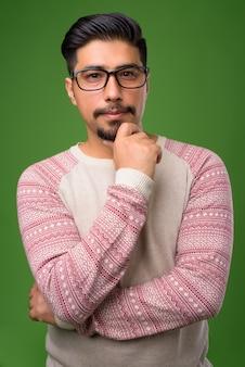 Молодой бородатый иранский мужчина на зеленом
