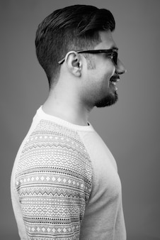 Young bearded iranian man wearing casual clothes against gray wall in black and white