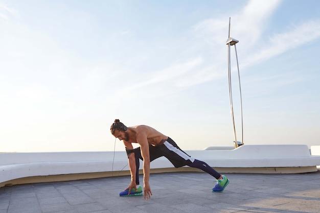 Giovane barbuto pareggiatore con corpo atletico in forma facendo esercizi di stretching, preparandosi per l'allenamento in riva al mare, ascoltando musica motivazionale.