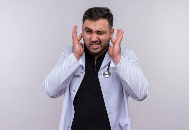 白衣を着た若いひげを生やした男性医師が聴診器で耳を閉じ、大きな音のノイズにイライラした表情で耳を閉じます