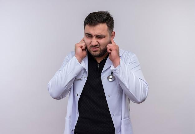 Молодой бородатый мужчина-врач в белом халате со стетоскопом закрывает уши пальцами с раздраженным выражением лица из-за шума громкого звука
