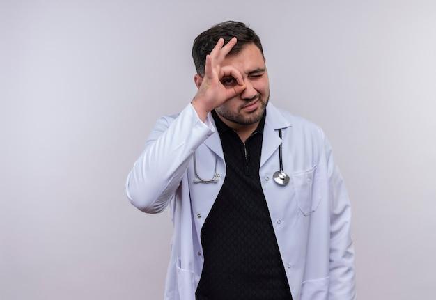 Giovane medico maschio barbuto che indossa camice bianco con lo stetoscopio che fa segno giusto guardando attraverso questa canzone sorpreso