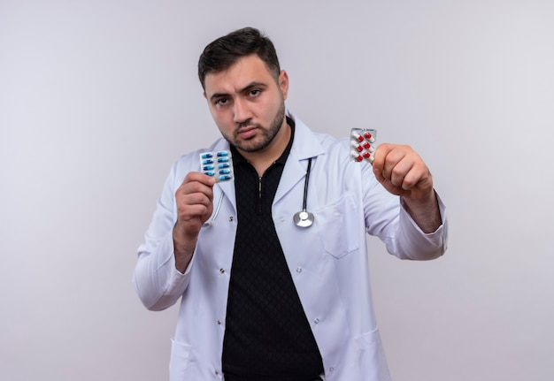 Giovane maschio barbuto medico indossa camice bianco con lo stetoscopio che tiene le bolle con le pillole che mostrano alla macchina fotografica con la faccia seria