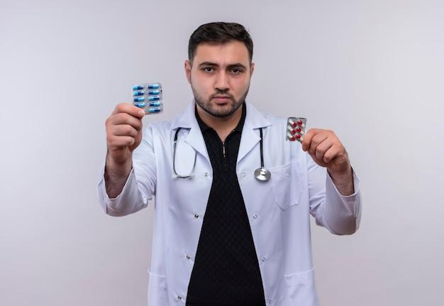 深刻な顔でカメラに見せてピルと水ぶくれを保持している聴診器で白衣を着ている若いひげを生やした男性医師