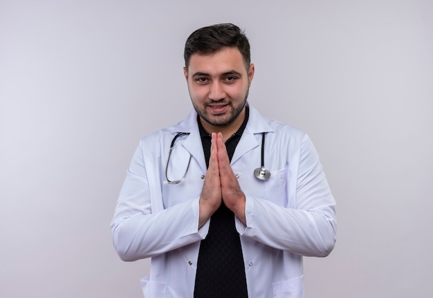 Young bearded male doctor wearing white coat with stethoscope holding hands together in prayer gesture feeling thankful and happy
