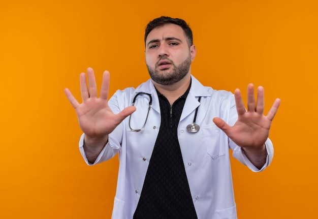 Young bearded male doctor wearing white coat with stethoscope holding out his hands making stop sign with fear expression