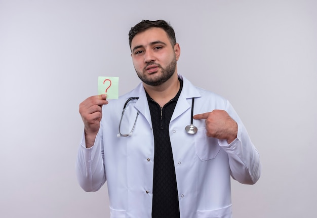 Young bearded male doctor wearing white coat with stethoscope holding reminder paper with question mark pointing with index finger to it