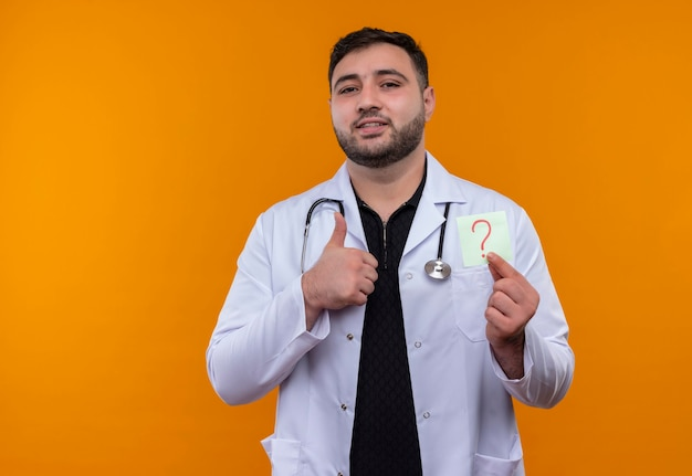 Young bearded male doctor wearing white coat with stethoscope holding reminder paper with question mark smiling showing thumbs up