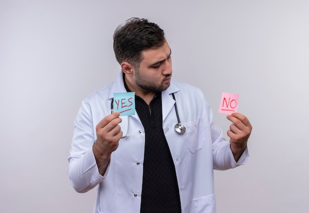 Young bearded male doctor wearing white coat with stethoscope holding reminder papers with words yes and no looking at them intrigued