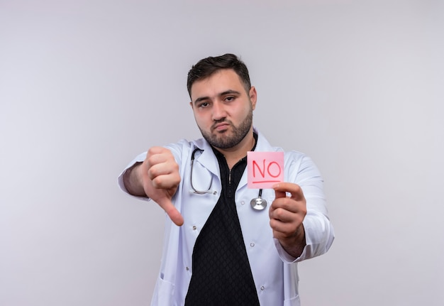 Молодой бородатый мужчина-врач в белом халате со стетоскопом, держащий напоминание, со словом, не выглядящим недовольным, демонстрирующим неприязнь