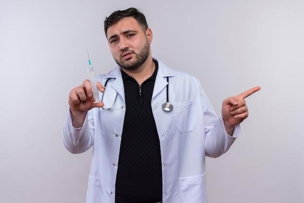 Молодой бородатый мужчина-врач в белом халате со стетоскопом держит шприц в замешательстве, указывая пальцем в сторону